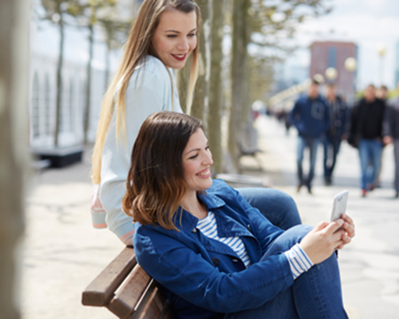 woman sitting on a bench looking at a phone